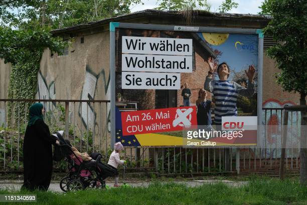 Muslim woman and children walk past an election campaign poster for the German Christian Democrats on May 23, 2019 in Goerlitz, Germany. Voters in...