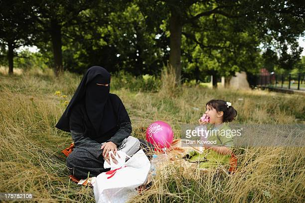 A muslim woman and girl sit in the shade in Burgess Park during an Eid celebration fun fair on August 8 2013 in London England The Muslim holiday Eid...