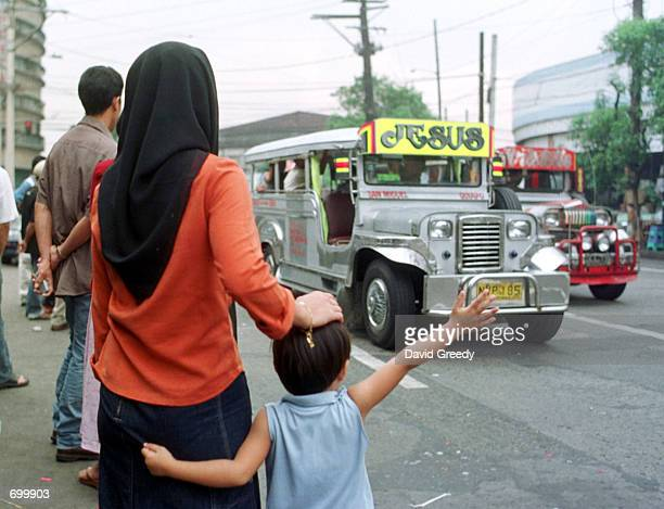 Muslim woman and her child flag down a jeepney outside the Manila Islamic Center of San Miguel February 8 2002 metro Manila Philippines The area is...