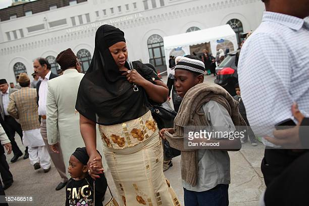 Muslim woman and her children leave after the departure of the Islamic Khalifa of the Ahmadiyya Muslim community Mirza Masroor Ahmad who spoke at...