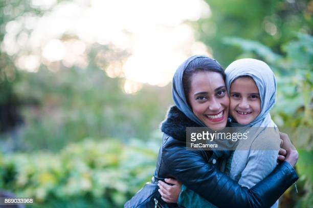 muslim woman and her daughter enjoying a day at the park. - muslim mother stock pictures, royalty-free photos & images