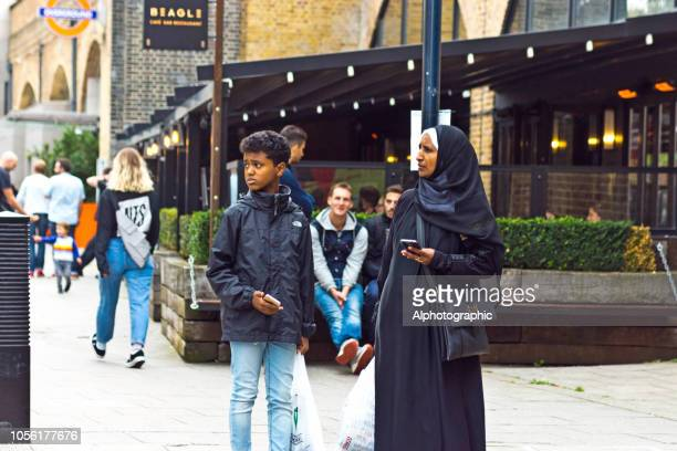 イスラム教徒の女性と彼女の息子のショッピングや携帯電話を使用して - ソマリア ストックフォトと画像