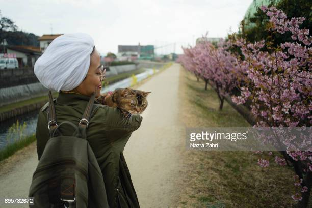 Muslim woman and pet cat in sakura park