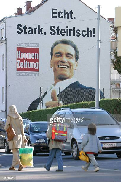 Muslim woman and two children walk past a massive billboard of newly elected California Governor Arnold Schwarzenegger that reads 'Real Strong...