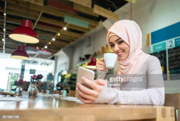 Muslim woman at a cafe texting on her mobile phone