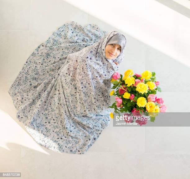 Muslim woman at home with flowers