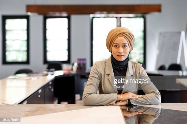 muslim woman at reception desk in modern office - malay hijab stock photos and pictures