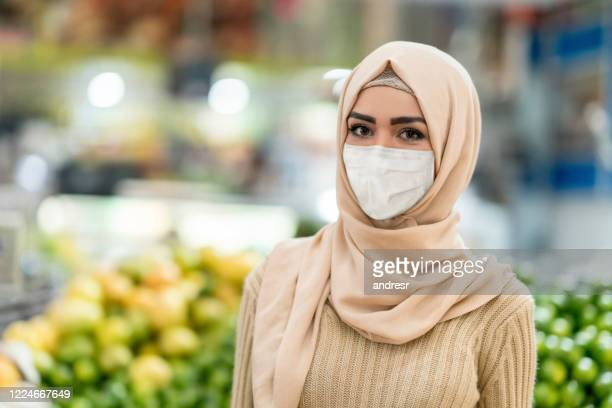 muslim woman buying essentials at a food market while wearing a facemask - iraq stock pictures, royalty-free photos & images