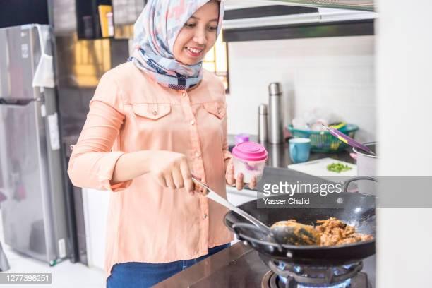 muslim woman cooking in kitchen - sal de cozinha - fotografias e filmes do acervo