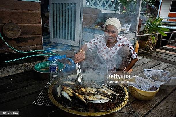 A muslim woman cooks fresh fish as she prepares lunch for her family at Kampung Air on November 7 2013 in Bandar Seri Begawan Brunei Darussalam...