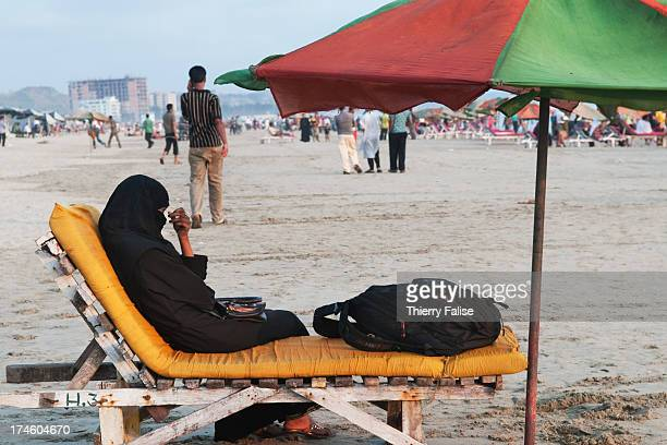 COX'S BAZAR BANGLADESH A Muslim woman covered in a black dress and veil sits on a deckchair on Cox's Bazar beach