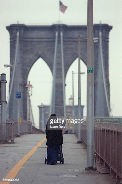 A Muslim woman crosses the Brooklyn Bridge with a baby stroller Photo by Jason Florio/Corbis Sygma