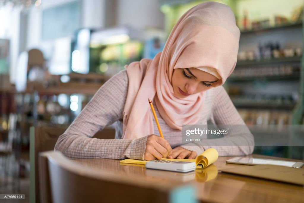 Muslim woman doing the books at a restaurant : Stock Photo