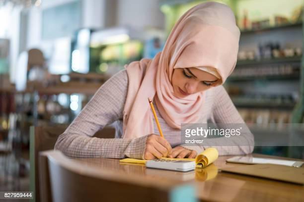 Die muslimische Frau, die die Bücher in einem Restaurant zu tun