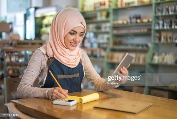 Muslim woman doing the books at a restaurant
