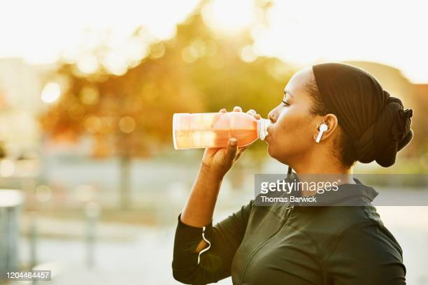 muslim woman drinking sports drink after working out in park on fall afternoon - カーキグリーン ストックフォトと画像