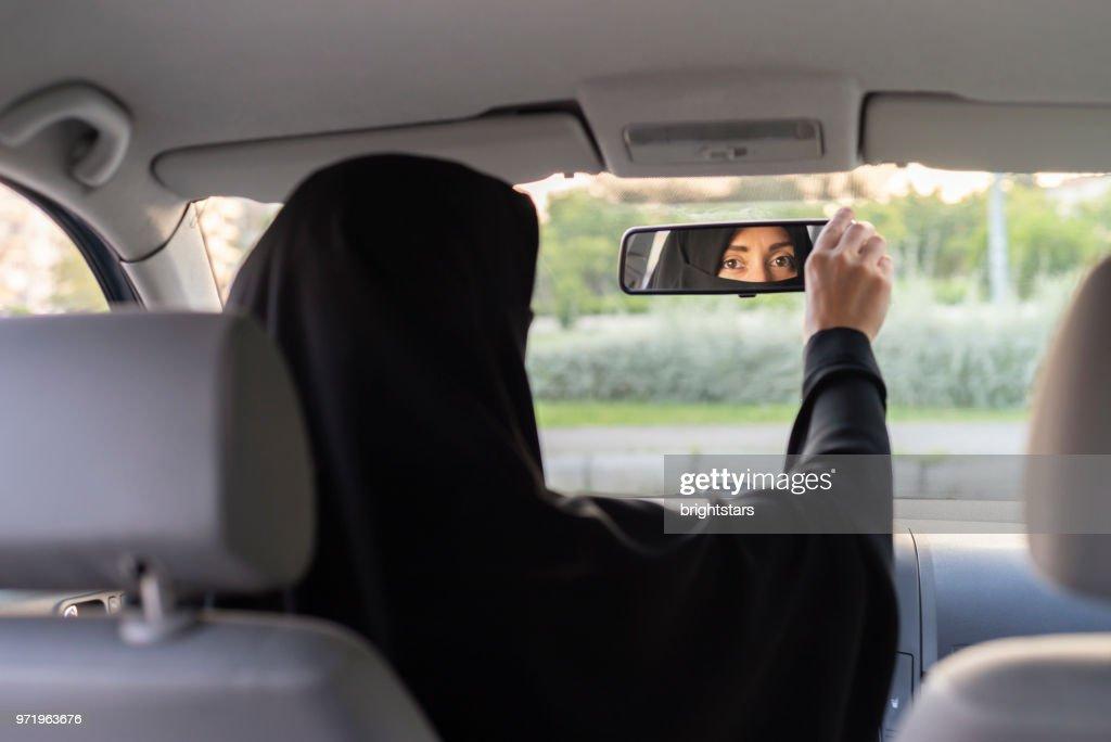 Muslim woman driving a car : Stock Photo