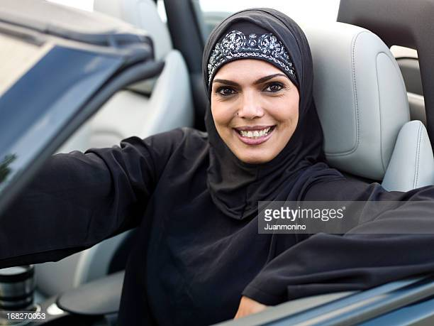 Muslim woman driving her convertible