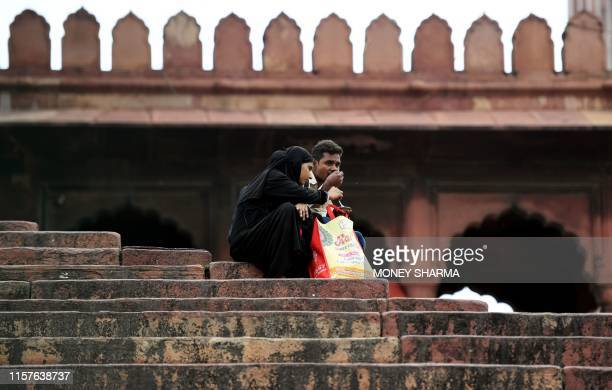 A Muslim woman eats as she sits on the stairs of Jama Masjid in the old quarters of New Delhi on July 25 2019 The ruling Bharatiya Janata Party...