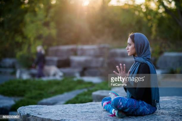 Muslim woman enjoying quiet meditation in park