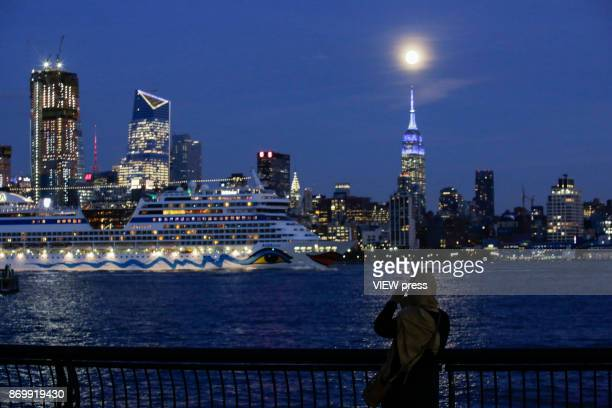 A muslim woman enjoys the moonrise over the Empire State Building and Manhattan skyline along the Hudson river on November 2 2017 in Hoboken NJ