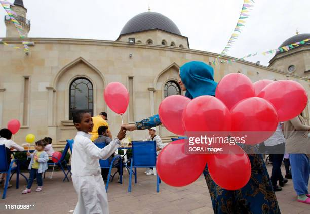 Muslim woman gives a balloon to a young boy at the ArRahma Mosque during the celebration Eid alAdha is the biggest celebration for Muslims in all...
