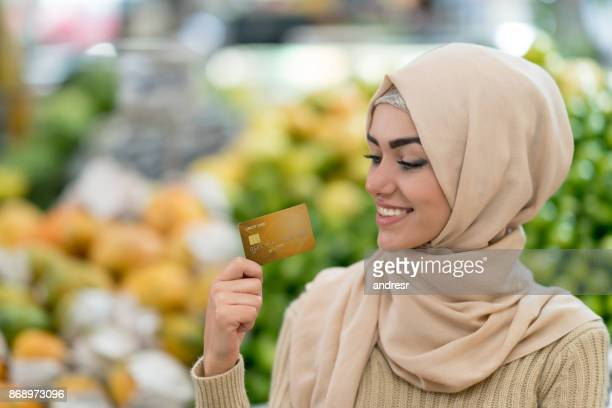 Muslim woman grocery shopping with a credit card