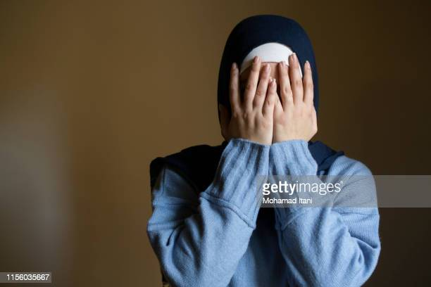 muslim woman hiding face with hands crying - hands covering eyes stock pictures, royalty-free photos & images