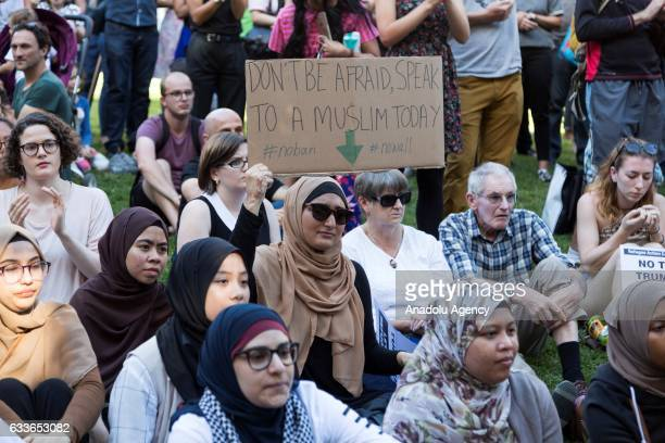 Muslim woman hold a placard reading 'Dont be afraid to speak to a muslim today' during a protest against US President Donald Trump and his recent...