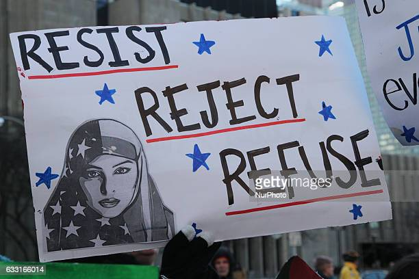 Muslim woman holding a sign saying 'reject resist refuse' during a massive protest against President Trump's travel ban outside of the US Consulate...