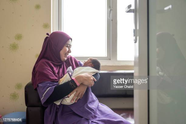 muslim woman holding newborn - modest clothing stock pictures, royalty-free photos & images