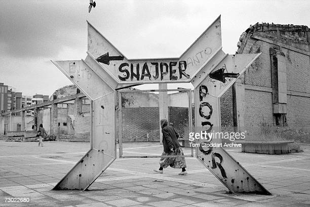 Muslim woman hurries past graffiti warning of snipers in a dangerous part of Sniper Alley. During the 47 months between the spring of 1992 and...