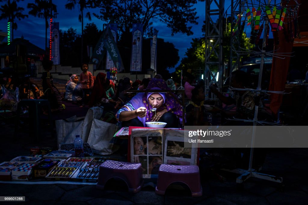 A muslim woman iftar on the first day of the holy month of Ramadan at the yard of Grand mosque on May 17, 2018 in Surabaya, Indonesia. Indonesia will begin observing Ramadan on Thursday where millions of Muslims begin the fasting from dawn-to-dusk for a month. For the Islamic State group, Ramadan has become a strategic time to strike as Indonesians faced an uptick of violence linked to the terrorist group during gruesome attacks at three churches and a police station around Surabaya which involved using children as suicide bombers.