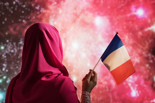 Muslim woman in a scarf holding flag of France during fireworks at night. 1200896652
