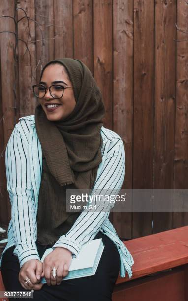 a muslim woman in olive-colored hijab, holding a book - muslimgirlcollection stock pictures, royalty-free photos & images