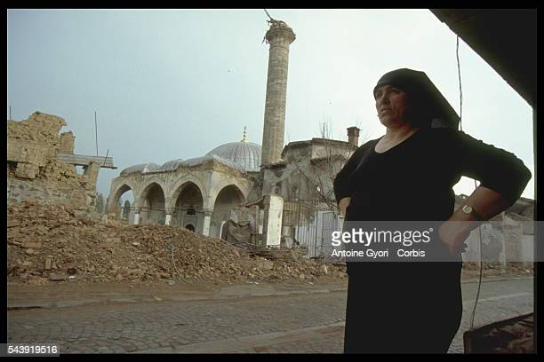 Muslim woman in Pristina, Kosovo, stands near a mosque destroyed by Serbian bombing during the Yugoslavian Civil War. In the 1990s, the Yugoslavian...