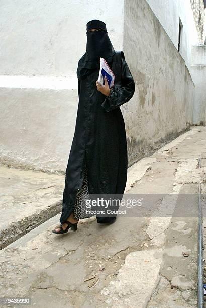 Muslim woman in traditional clothing (abbaya) walking in one of Lamu's narrow streets. Kenya, Africa