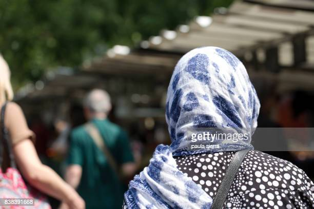 a muslim woman is buying in a market - 宗教的なベール ストックフォトと画像