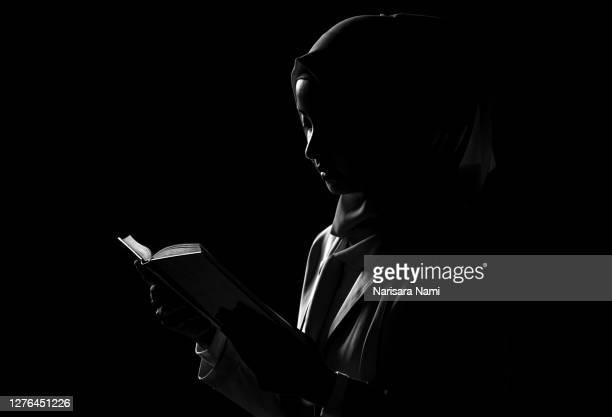 a muslim woman is reading the quran. the quran is indicated as the guided book for all muslims and it is the direction to be on the heaven of god. mosque, islam, religion, and knowledge concept. - 礼拝 ストックフォトと画像