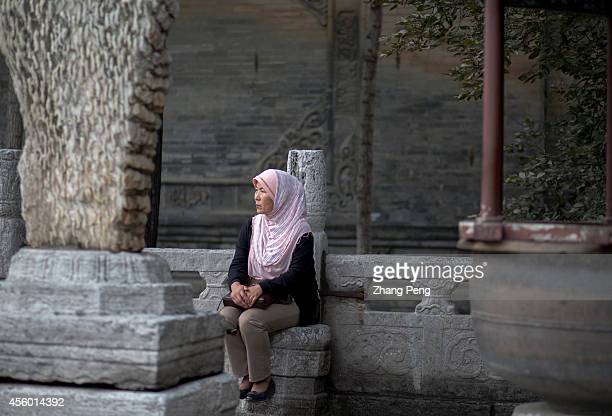 XI'AN SHAANXI CHINA A Muslim woman is waiting outside the main hall for worship of the Xi'an Great Mosque Her husband is making worship in the Hall...