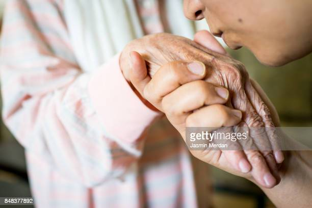 muslim woman kissing hand of her old mother - respekt stock-fotos und bilder