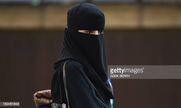 A Muslim woman looks on after attending prayers at the Regent's Park Mosque in London on August 19 2012 Muslims around the world celebrate Eid alFitr...
