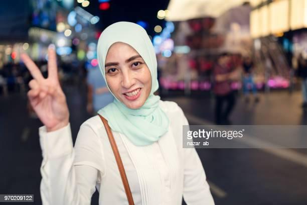 Muslim woman making winning gesture.