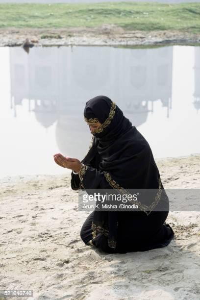 Muslim Woman offering Namaz in front of Taj Mahal Agra Uttar Pradesh