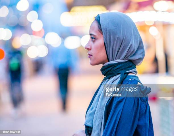 A muslim woman on a city street gazing into the distance