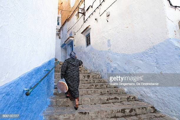 Muslim woman on stairs in Chefchaouen, Morocco