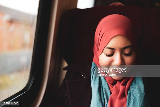 muslim woman on the train - islam stock pictures, royalty-free photos & images