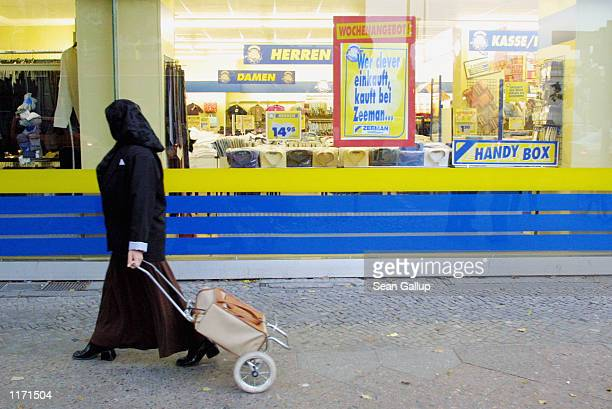 Muslim woman passes a shop October 10 2001 in Berlin's heavilyMuslim Neukoelln district Investigators are revealing that Germany has been a major hub...
