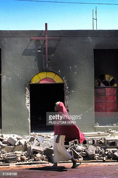Muslim woman passes the Evangelical Church of West Africa burned by Muslim rioters in Kaduna 22 November 2002 More than a hundred people were feared...