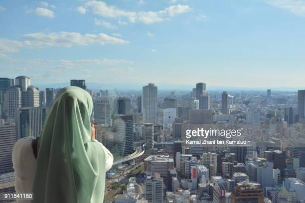 A muslim woman photographing a city view